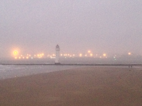 Before darkness falls a sea mist rolls in around the lighthouse on the Mersey estuary